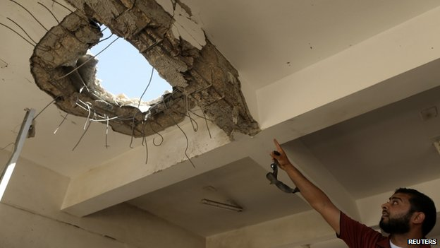 A teacher points to a hole in the ceiling after a building was bombed by a Libyan warplane at a university in Benghazi (1 June 2014) Forces loyal to renegade General Khalifa Haftar carried out air strikes in Benghazi on Sunday
