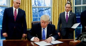 U.S. President Donald Trump signs an executive order on U.S. withdrawal from the Trans Pacific Partnership while flanked by Vice President Mike Pence (L) and White House Chief of Staff Reince Priebus (R) in the Oval Office of the White House in Washington January 23, 2017. REUTERS/Kevin Lamarque
